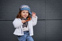 Model child hip-hop.baby in a baseball cap. Model child hip-hop.Children`s fashion wear jeans posing against grey wall, minimalist street style children`s Stock Images