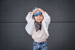 Model child hip-hop.baby in a baseball cap. Model child hip-hop.little baby girl in the baseball cap happy dancing in the background of the gray wall.Children`s Stock Photos