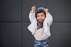 Model child hip-hop.baby in a baseball cap. Model child hip-hop.little baby girl in the baseball cap happy dancing in the background of the gray wall.Children`s Stock Image