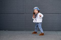 Model child hip-hop.baby in a baseball cap. Model child hip-hop.little baby girl in the baseball cap happy dancing in the background of the gray wall.Children`s Royalty Free Stock Images