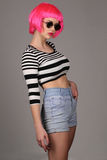 Model with circle sunglasses and pink wig. Close up. Gray background Royalty Free Stock Images