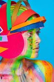 Model with colorful abstract makeup in multicolored helmet Royalty Free Stock Image