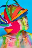 Model with colorful abstract makeup in multicolored helmet Stock Photos
