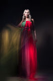 Model in colorful dress on black background Stock Photo
