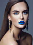 Model with colorful makeup with blue lips  and jewelry Royalty Free Stock Photo