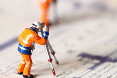 Model construction worker building plans D. Photograph of scale model construction figure on a set of building plans Stock Photography