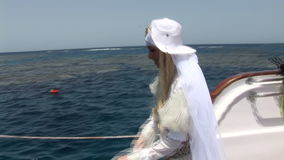 Model in costume of pirate jumping into water from ship in Red Sea. Filming a movie. Young girl smiling at camera stock video footage