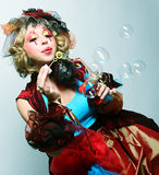 Model with creative make-up blowing soap bubbles. Stock Photo