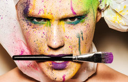 Model with creative makeup. Close-up portrait of young woman with unusual makeup. Model holding makeup brash in her mouth. Woman posing with paint drops over her Stock Images