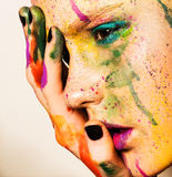 Model with creative makeup. Close-up portrait of young woman with unusual makeup. Model posing with paint drops over her face. Creative makeup Royalty Free Stock Photo