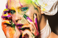Model with creative makeup. Close-up portrait of young woman with unusual makeup. Model posing with paint drops over her face. Creative makeup Royalty Free Stock Photography