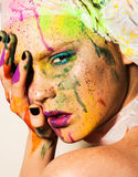 Model with creative makeup. Close-up portrait of young woman with unusual makeup. Model posing with paint drops over her face. Creative makeup Stock Images