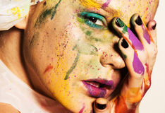 Model with creative makeup. Close-up portrait of young woman with unusual makeup. Model posing with paint drops over her face. Creative makeup Stock Photo