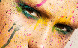 Model with creative makeup. Close-up portrait of young woman with unusual makeup. Model posing with paint drops over her face. Creative makeup Stock Image