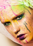 Model with creative makeup. Close-up portrait of young woman with unusual makeup. Model posing with paint drops over her face. Creative makeup Royalty Free Stock Photos
