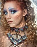 Model with creative makeup with a triangular necklace. Portrait of a beautiful girl.
