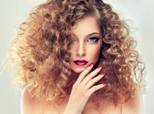 Model with curly hair. Bright make up and red manicure stock photos
