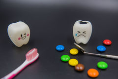 Model Cute toys teeth and colorful candy in dentistry on a black background Stock Photography
