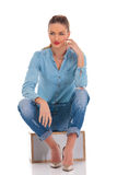 model in denim pose seated in studio background with hand on knee touching face royalty free stock image