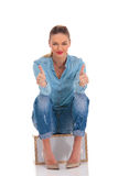 Model in denim pose seated in studio background while showing vi stock photography
