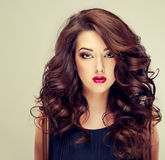 Model with dense, curly hair. And bright red lipstick. Luxury fashion style, manicure, cosmetics and make-up Royalty Free Stock Photography