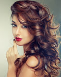 Model with dense, curly hair. And bright red lipstick. Luxury fashion style, manicure, cosmetics and make-up Stock Photography
