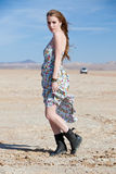 Model in desert with car in distance Stock Photo