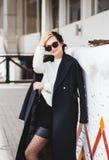 Model die van de manier het mooie vrouw een donkere laag en een witte sweater, in zonnebril dragen, die over witte achtergrond st stock foto's