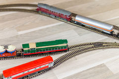 Model diesel engines pull freight trains. On light wooden floor, playtime for kids and adults stock photography