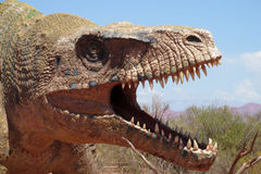 The model of a dinosaur head. The statue, a model dinosaur standing on a red dry sand between the rocks. Artificial dinosaur. Jurassic Park. Models of dinosaurs stock photo