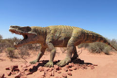 The model of a dinosaur. The statue, a model dinosaur standing on a red dry sand between the rocks. Artificial dinosaur. Jurassic Park. Models of dinosaurs in royalty free stock images