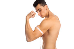 Model doing measurements of his biceps Royalty Free Stock Photos