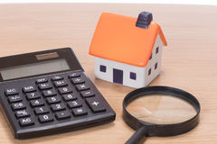 Model dom wśród magnifier z kalkulatorem fotografia royalty free