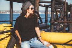 Model dragende duidelijke t-shirt en zonnebril die over straat stellen wal royalty-vrije stock fotografie