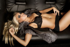 Model dressed in fur laying on sofa Stock Photo