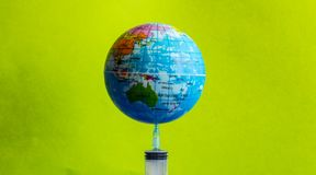 The model earth on the syringe with the green background -image royalty free stock image