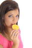 Model eating an orange slice. Shot of a model eating an orange slice Stock Photography