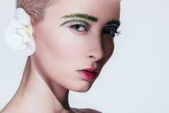 Model in een schoonheid die met bloem op witte achtergrond wordt geschoten stock fotografie