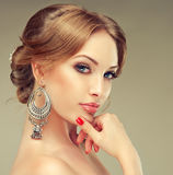 Model with elegant hairstyle. Big oriental earings and red nails Stock Image