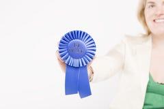 Model Employee. Woman holding blue ribbon toward camera Royalty Free Stock Images