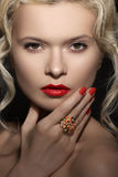 Model face, red lips make-up, manicure & jewelry ring. Beauty portrait of model face with bright lips make-up, manicure and big cocktail ring. Blond curly hair Stock Image