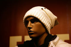 Model face in shop window. A mannequin's face wearing a white knitted hat and matching cream jacket with upturned  collar in a fashion shop window Royalty Free Stock Images