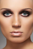 Model with fashion smoky eyes make-up & soft skin. Front portrait of sensual woman model with elegant fashion make-up on gray background royalty free stock images