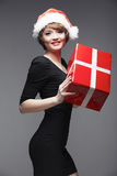 Model fashion woman hold Christmas gift. Santa wom Stock Photos