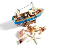 Model fishing boat with shells and starfishes on the white background Stock Images