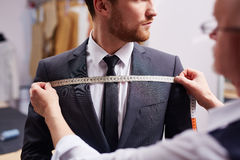 Model Fitting in Atelier. Mid section portrait of tailor fitting bespoke suit to model Stock Photo