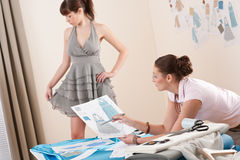 Model fitting by female fashion designer Royalty Free Stock Photography