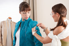Model fitting by female fashion designer Stock Photo