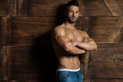 Model Flexing Muscles Near the Wooden Wall. Healthy Young Man Standing Strong Against a Wooden Wall and Flexing Muscles While Wearing Blue Jeans - a Place for Royalty Free Stock Photos