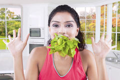 Model with full mouth of spinach Stock Photo